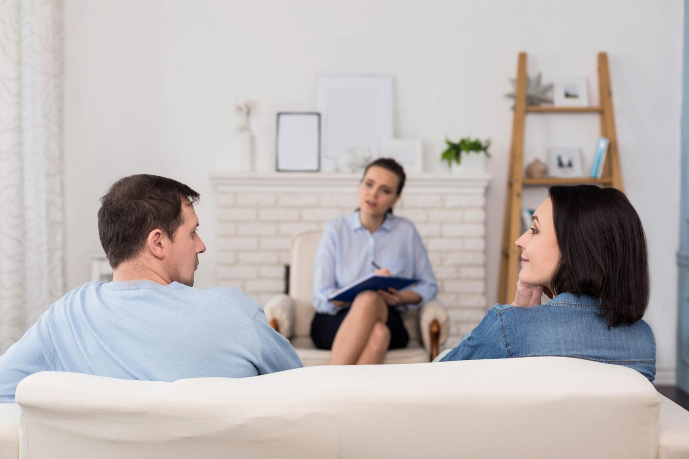 A couple during a session with counsellor in the middle sitting in a bright room