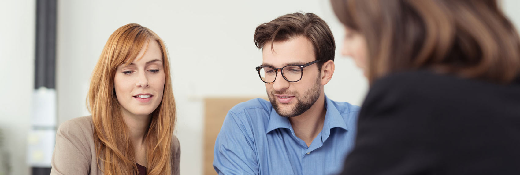 A happy young couple in bright room listening to professional woman in suit