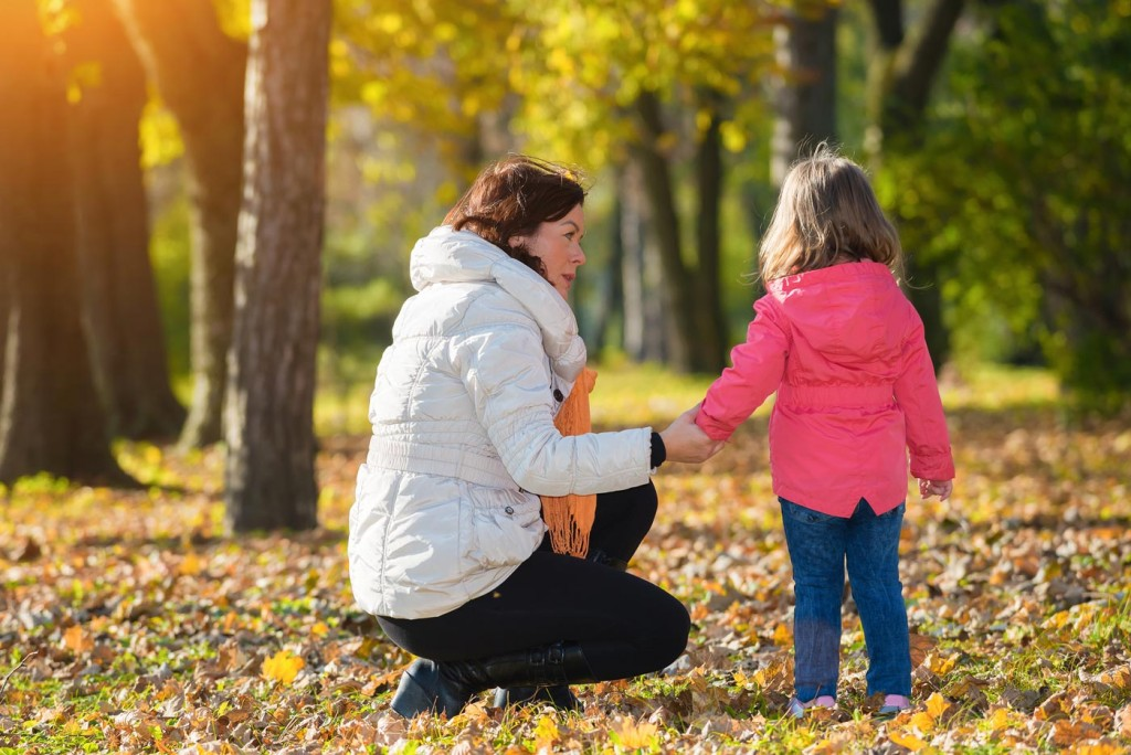 A woman in white jacket kneeling down to the child's eye level in the middle of autumn forest scenery